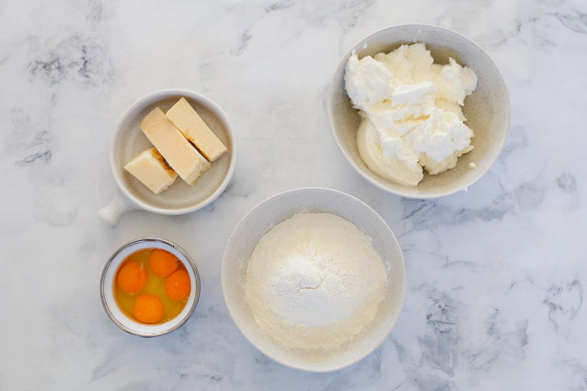 Huevos, harina, parmesano y ricotta en cuencos.