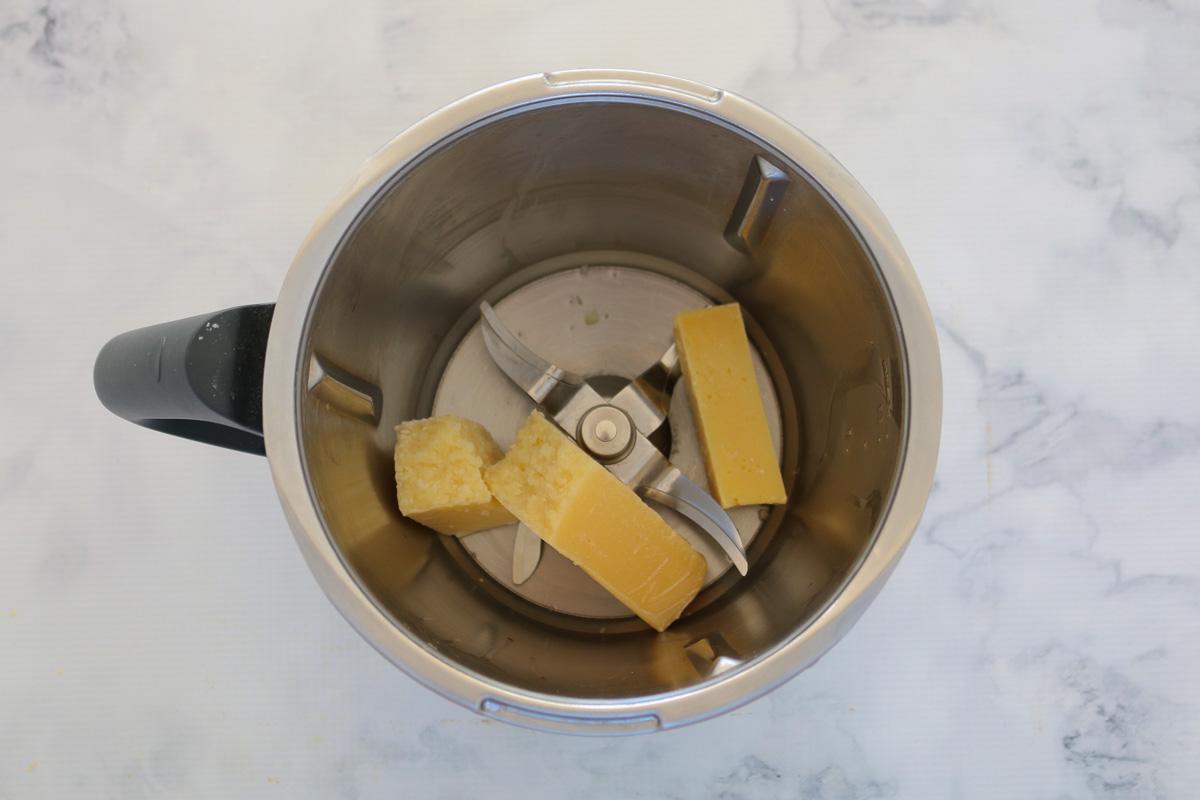 Trozos de queso parmesano en un bol Thermomix.