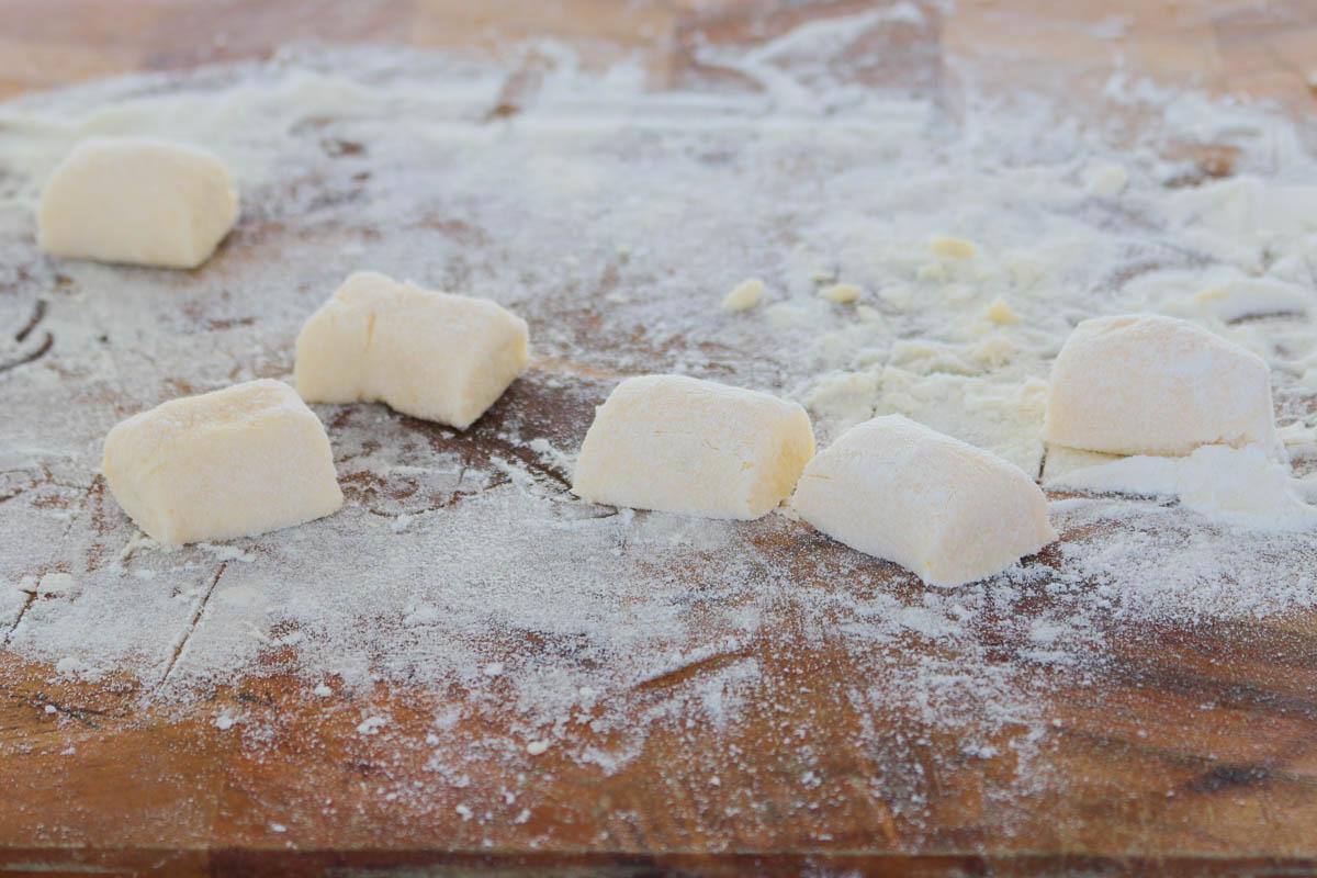 Ñoquis caseros cortados en trozos sobre una tabla enharinada.
