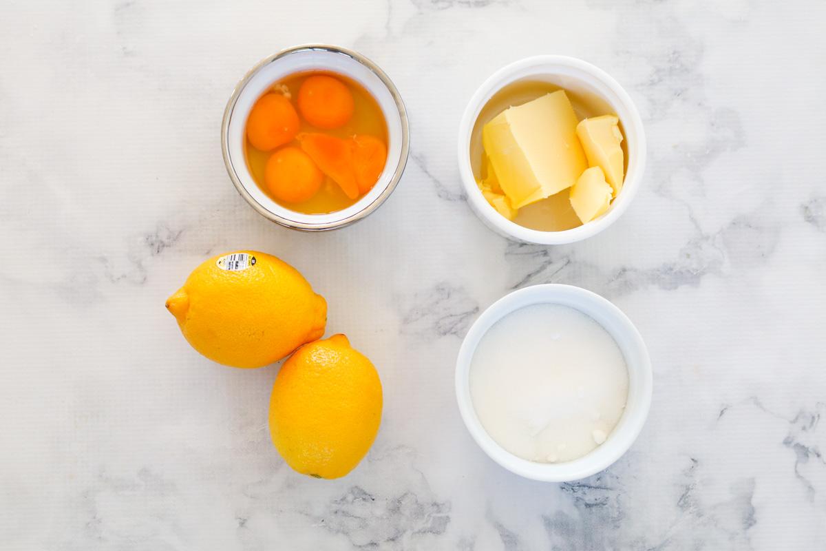 Mantequilla, azúcar, limones y huevos en cuencos.