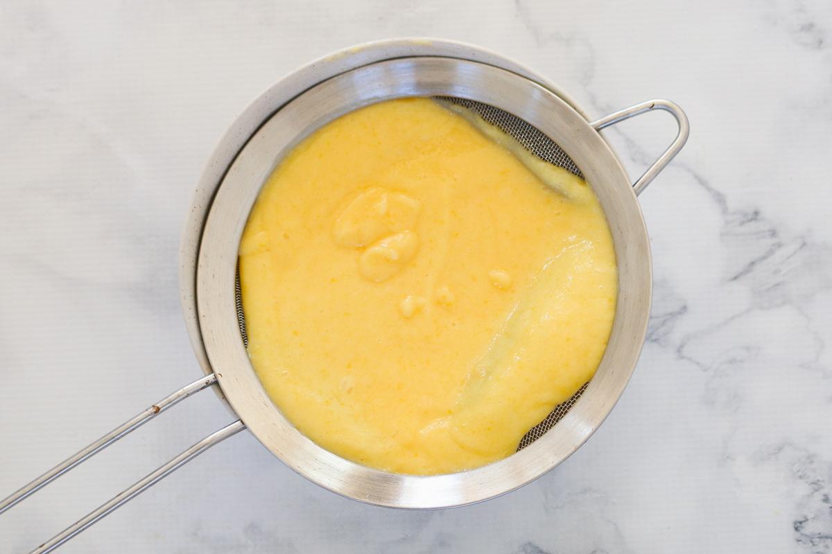 Cuajada de limón en un colador de plata.