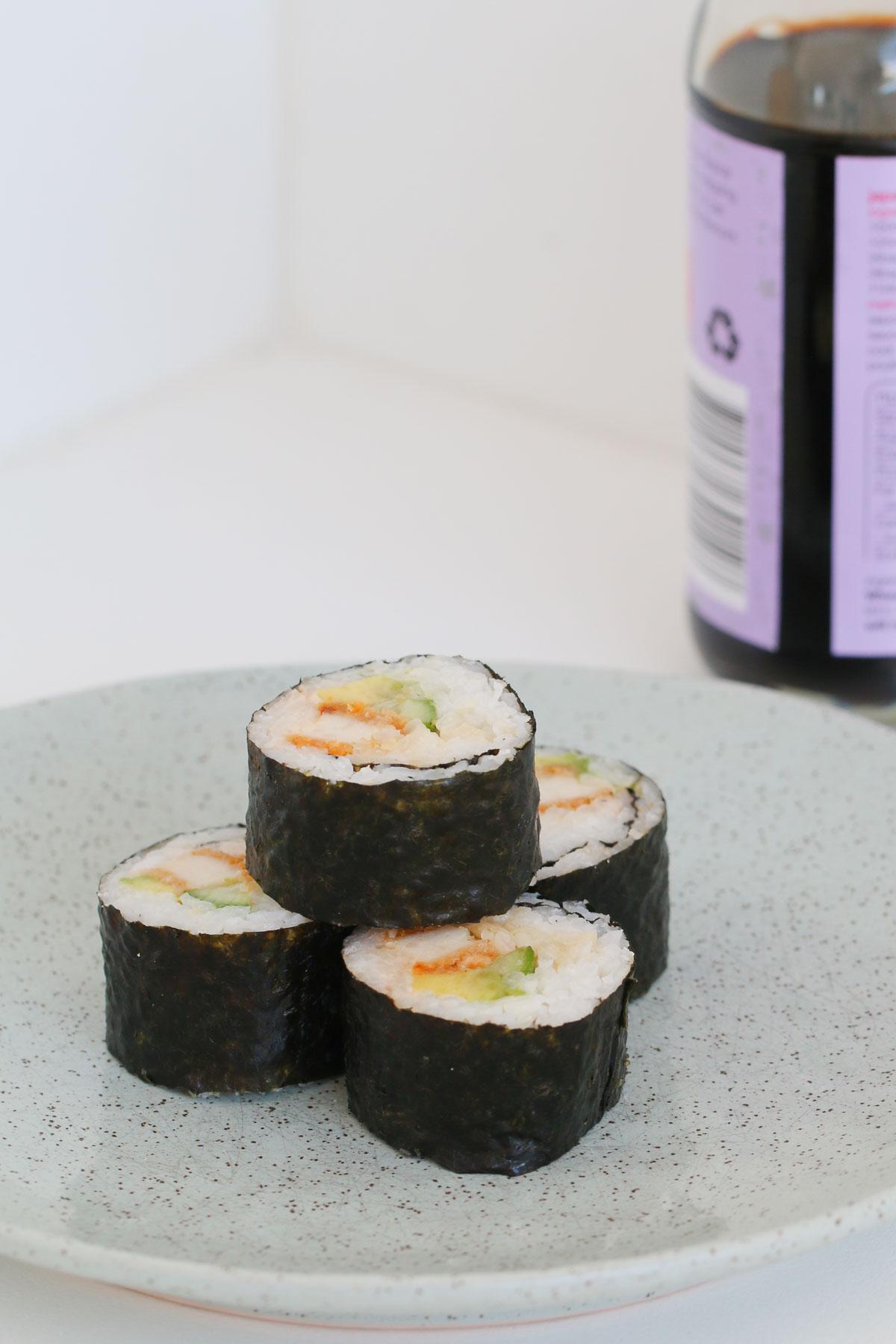 Sushi Thermomix casero con una botella de salsa de soja de fondo.