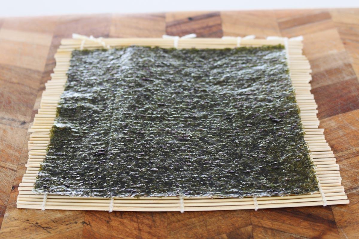 Una hoja de nori sobre una estera de bambú.