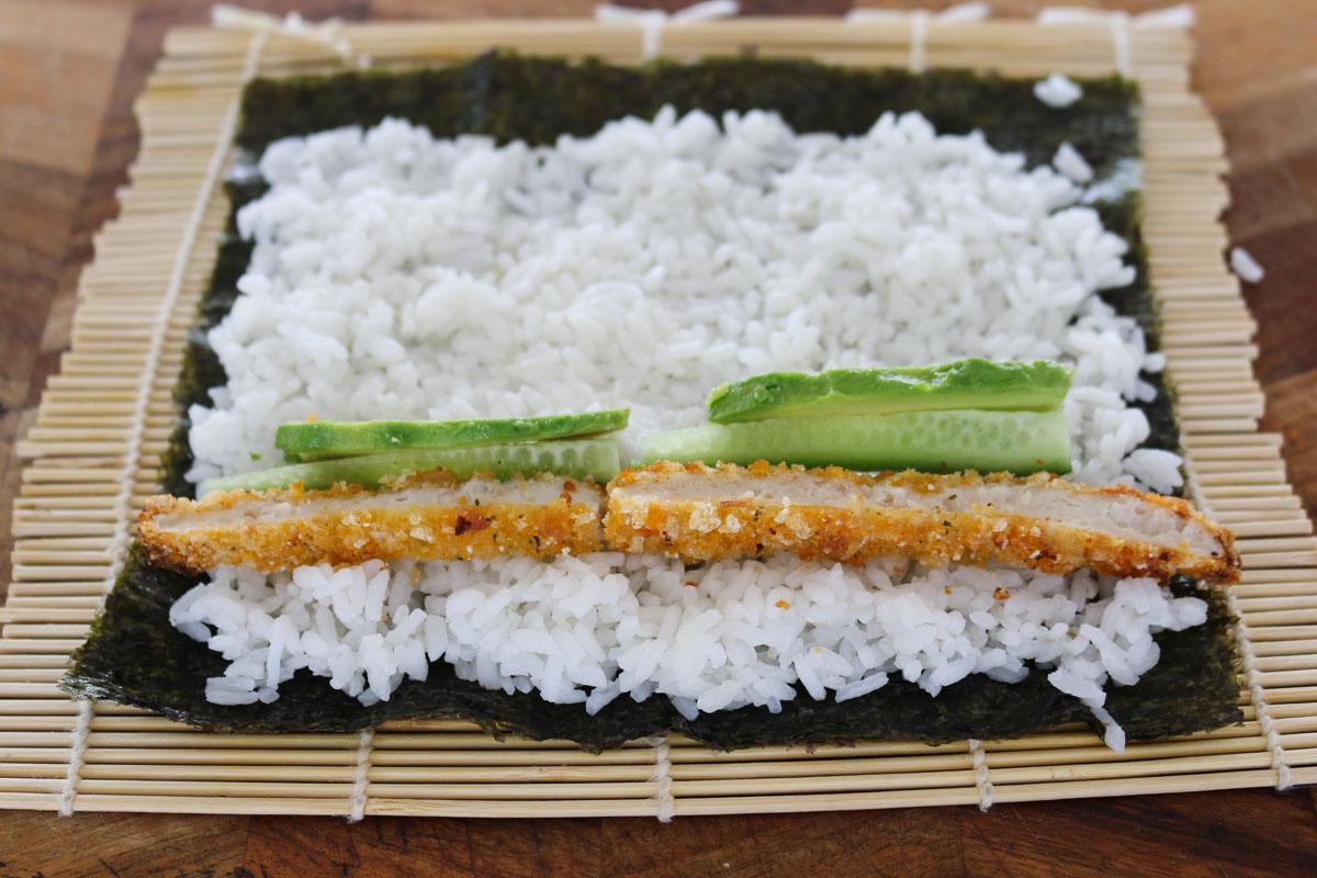 Pollo, pepino y aguacate sobre arroz de sushi en una hoja de nori.