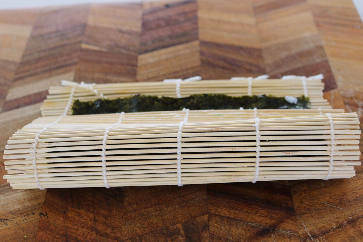 Una estera de bambú enrollando un rollo de sushi.