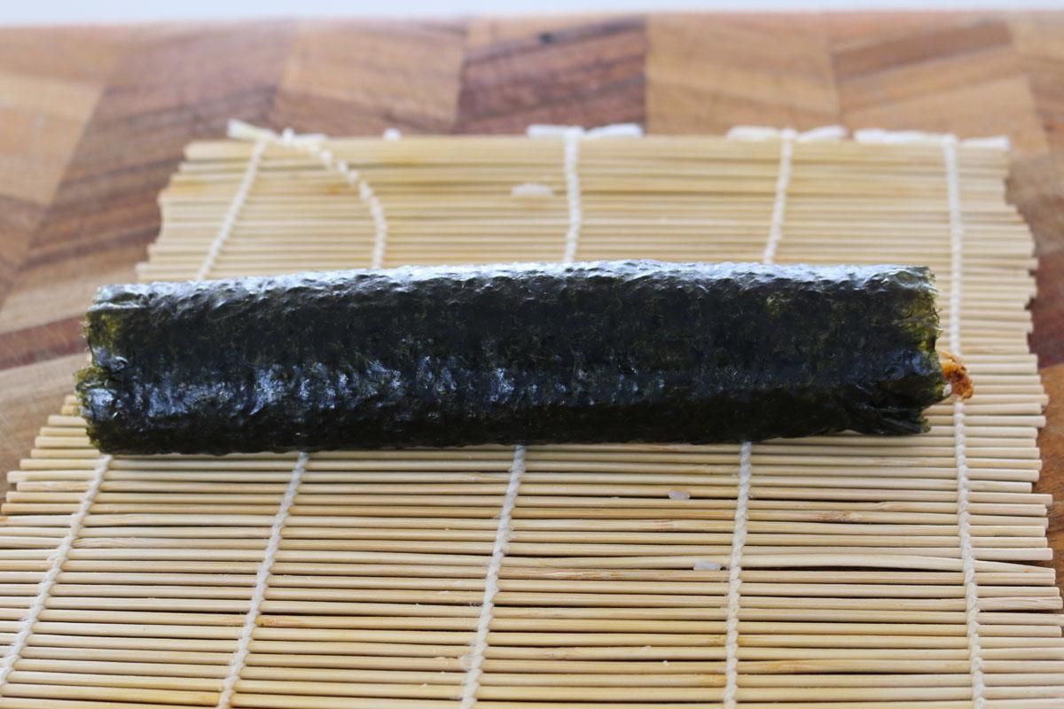 Rollo de sushi enrollado sobre una estera de bambú.