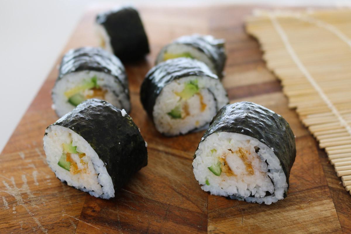 Trozos de sushi casero se cortan en una tabla de cortar.