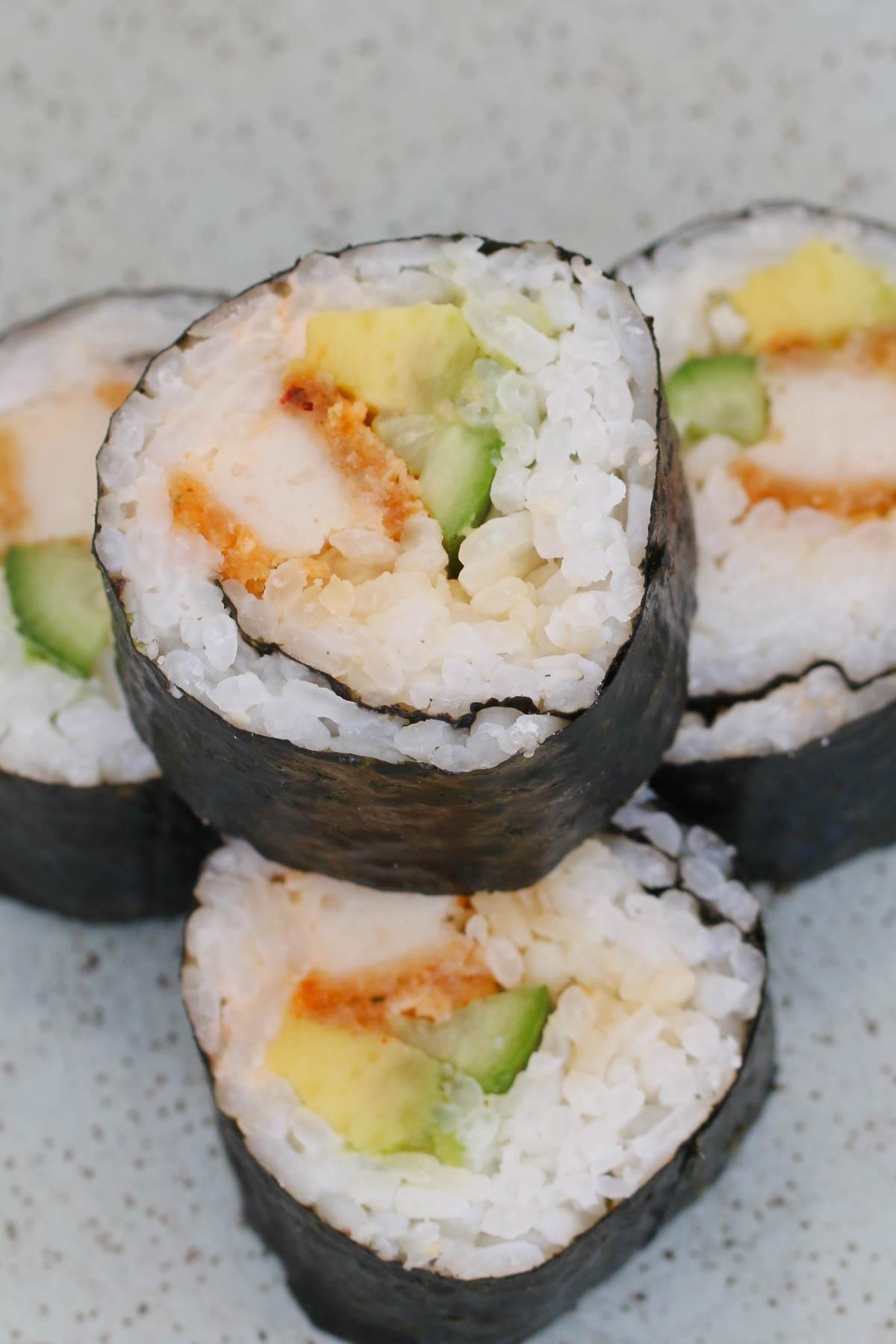 Una pila de sushi con pollo y aguacate en un plato.