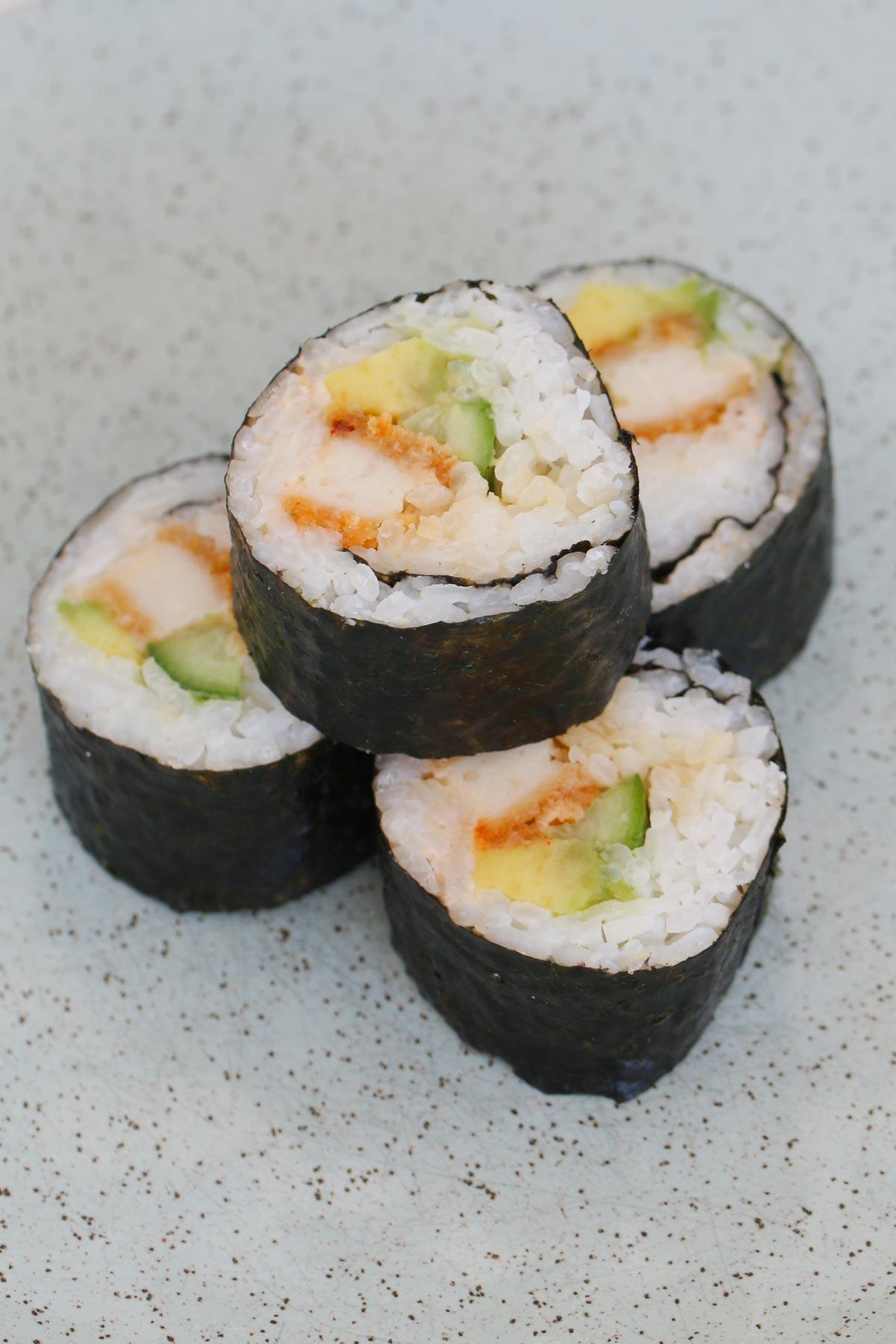 Una pila de arroz blanco, pollo y aguacate envuelto en hojas de nori.